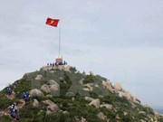 Youths build flagpole at north-east outpost island